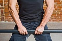 Bodybuilder que hace ejercicio de brazos con una barra Foto de archivo libre de regalías