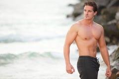 Bodybuilder que presenta en la playa Imagen de archivo