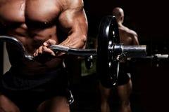 Bodybuilder con el Barbell delante del espejo oscuro Fotografía de archivo