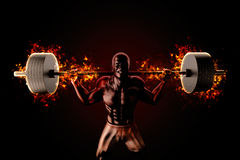 Bodybuilder raises flaming barbell Stock Image