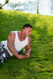 Bodybuilder Resting And Holding Water Bottle Stock Photo