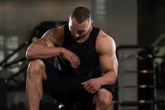 Bodybuilder se reposant au banc Photos libres de droits
