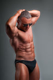 Bodybuilder with a shades. Muscular man in a speedo, bodybuilder with a shades Royalty Free Stock Photography