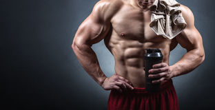 Bodybuilder with a shaker. Bodybuilder after a workout with a shaker on a dark background stock image