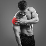 Bodybuilder Shoulder pain. Muscular shirtless man with shoulder pain over gray background. Concept with highlighted glowing red spot royalty free stock image