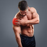 Bodybuilder Shoulder pain. Muscular shirtless man with shoulder pain over gray background. Concept with highlighted glowing red spot royalty free stock photography