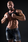 Bodybuilder. Showing his muscles on dark background Royalty Free Stock Photography