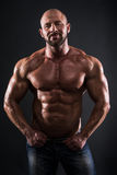 Bodybuilder. Showing his muscles on dark background Royalty Free Stock Photo