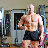 Bodybuilder showing thumbs up in gym Royalty Free Stock Photo