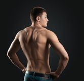 Bodybuilder shows dorsi. Bodybuilder showing muscles back in the dark Royalty Free Stock Photography