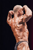 Bodybuilder shows his best back double biceps pose Stock Photography
