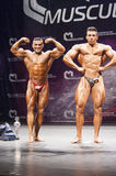 Bodybuilder shows his front double biceps pose on stage Royalty Free Stock Photos