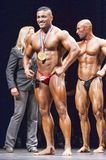 Bodybuilder shows his medal proudly on stage Royalty Free Stock Photography
