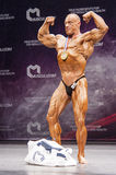 Bodybuilder shows his physique and his gold medal on stage Stock Photography