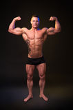 Bodybuilder shows muscles. On a dark background Stock Photo