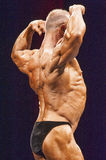 Bodybuilder shows muscular back on stage in championship Stock Photos