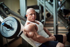 Bodybuilder sits on a simulator Royalty Free Stock Photography