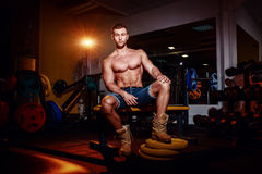 Bodybuilder sits on a weight bench, he takes a break. Muscular man at a workout place in a gym and smiling to camera. Royalty Free Stock Photos