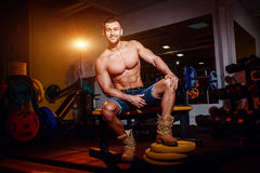Bodybuilder sits on a weight bench, he takes a break. Muscular man at a workout place in a gym and smiling to camera. Royalty Free Stock Images