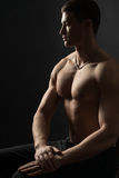 Bodybuilder sitting and looking sideways Stock Photo