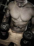 Bodybuilder sitting with weights in the gym. Bodybuilder standing with a dumbbell after training in the gym stock image