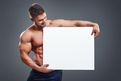 Bodybuilder with six pack holding white poster Royalty Free Stock Photo