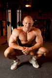 Bodybuilder sonriente en sitio del entrenamiento Imagen de archivo libre de regalías