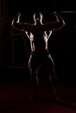 Bodybuilder Standing In The Gym And Flexing Muscles Royalty Free Stock Images