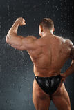 Bodybuilder stands in rain back to camera Royalty Free Stock Images
