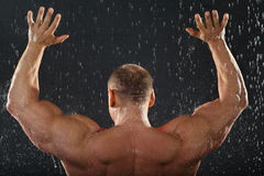 Bodybuilder stands in rain back to camera Stock Image