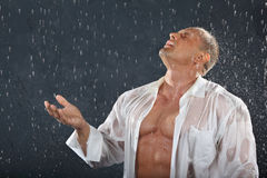 Bodybuilder stands in rain and catches drops. Tanned bodybuilder wearing white wet shirt stands in rain and catches drops by hand and mouth. Andrei Popov is Stock Photos