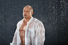 Bodybuilder stands in rain with closed eyes. Tanned bodybuilder wearing white wet shirt stands in rain with closed eyes. Andrei Popov is Bodybuilding Champion of Royalty Free Stock Photos