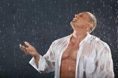 Bodybuilder steht im Regen und fängt Tropfen ab Stockfotos