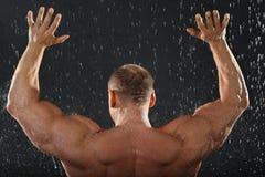 Bodybuilder steht im Regen zurück zu Kamera Stockbild