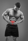 Bodybuilder Stomach ache. Young athlete having a stomach ache and palpating belly zone. Highlighted red spot concept royalty free stock photos