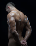 Bodybuilder and strip theme: beautiful with pumped muscles naked man posing in the studio on a dark background Royalty Free Stock Images