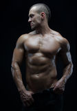 Bodybuilder and strip theme: beautiful with pumped muscles naked man posing in the studio on a dark background Stock Photo