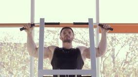 Bodybuilder szkolenie, mięśniowa atleta z pięknym sportowym ciałem ciągnie w górę symulanta na podczas władza treningu przy sport zbiory