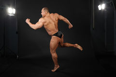 Bodybuilder takes graceful pose of running Stock Image
