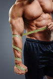 Bodybuilder with tape measure. Closeup of bodybuilder holding tape measure. Cropped image of muscular arm holding measuring tape isolated over gray background royalty free stock images
