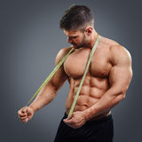 Bodybuilder with tape measure. Muscular sports man tries to measure his neck muscles with measuring tape isolated over gray background. Confused bodybuilder stock photos