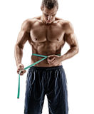 Bodybuilder with tape measures the size of the waist Stock Photos