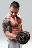 Bodybuilder with a tattoo lifting weights, closeup Stock Photos