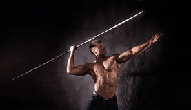 Bodybuilder throwing javelin Stock Photo