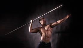 Bodybuilder throwing javelin. Side view of muscular bodybuilder with bare chest throwing javelin, studio background Stock Photo