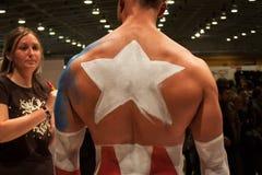 Bodybuilder tijdens een lichaam het schilderen zitting bij de Tatoegeringsovereenkomst van Milaan Stock Afbeeldingen