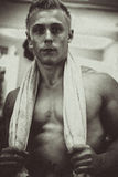Bodybuilder with towel around neck. Bodybuilder standing with a towel around his neck. Monochrome royalty free stock photography