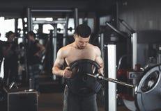 Bodybuilder trainiert mit schwerer Ausrüstung zuhause stockbilder