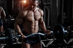 Bodybuilder training biceps with barbell in the gym Stock Photos