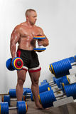 Bodybuilder training with dumbbells Royalty Free Stock Image